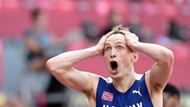 Karsten Warholm, les mains sur la tête, les yeux grands ouverts, encore surpris de sa performance.