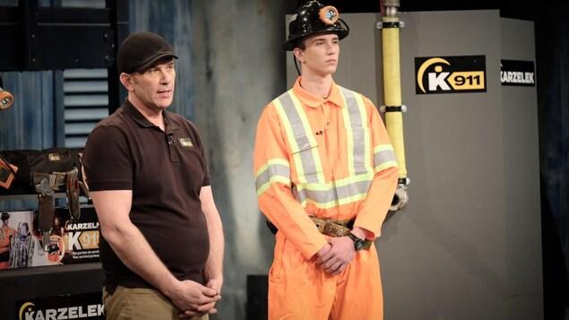 Un homme fait une présentation aux côtés d'un jeune homme portant une combinaison de sécurité et un casque de mine.