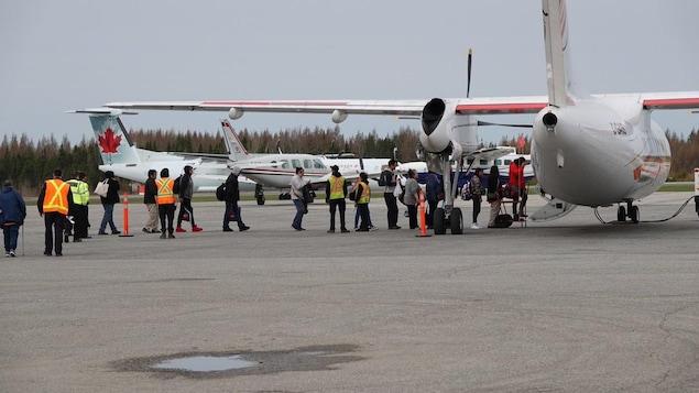 Des gens sur le tarmac qui montent à bord d'un avion.