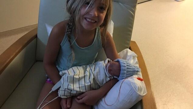 Une enfant souriante, assise dans un fauteuil, tient un nouveau-né dans ses bras.