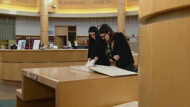Kate Rozon (à gauche), archiviste pour les Archives provinciales de l'Alberta, présente à la journaliste Virginie Dallaire (à droite), un registre d'inscriptions d'élèves au pensionnat de Red Deer, datant de 1884.