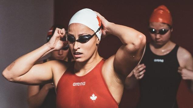 Une nageuse en maillot de bain replace ses lunettes de natation.