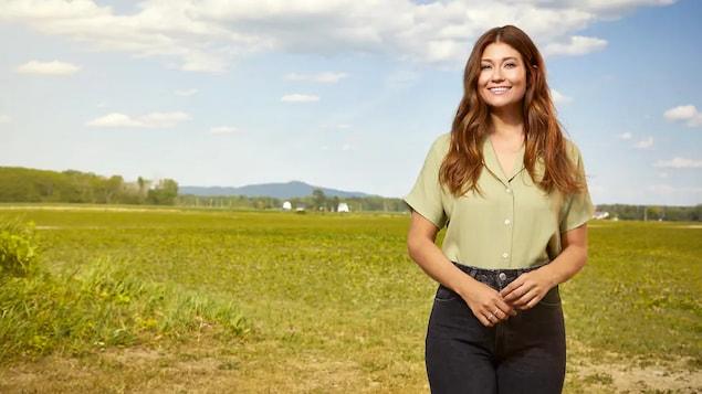 L'humoriste Katherine Levac sourit  devant un champ de verdure.