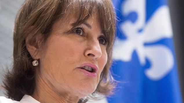 Kathleen Weil parle devant un drapeau du Québec, qui se trouve en arrière plan.