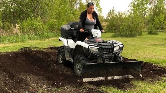 Katie Pchajek creuse un bout de terrain au volant d'un véhicule tout-terrain sur lequel une pelle a été ajoutée.