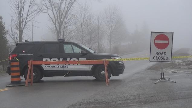 Un véhicule de police, derrière un barrage routier, une journée brumeuse.