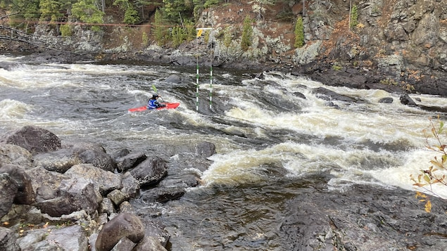 Un kayakiste dans une rivière à fort débit.