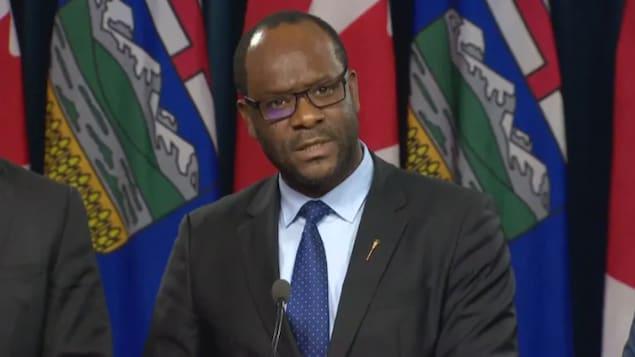 Kaycee Madu répond à une question alors qu'il est sur un podium.