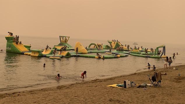 À Kelowna, des enfants jouent sur le lac Okanagan sous un ciel enfumé par les feux de forêt, le 30 juillet 2021.