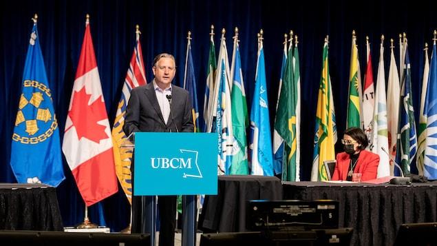 Kennedy Stewart, maire de Vancouver, à un pupitre du Congrès de l'Union des municipalités de la Colombie-Britannique, devant de multiples drapeaux.