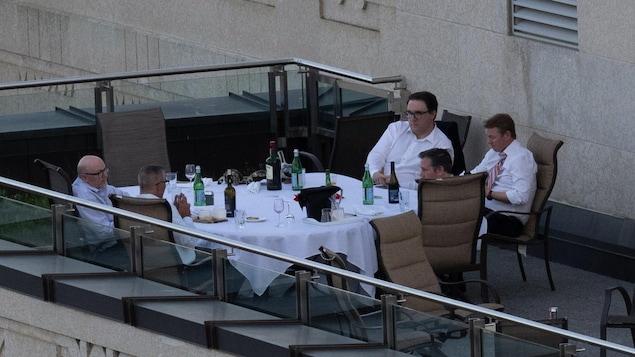 Le premier ministre Jason Kenney, les ministres Jason Nixon, Tyler Shandro et Travis Toews ainsi qu'un homme non identifié discutent à une table.