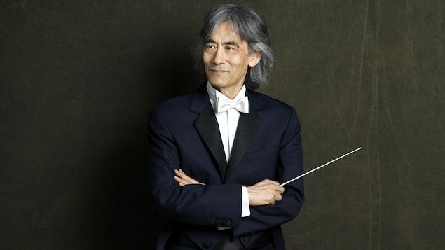 Un homme avec une baguette de chef d'orchestre fait la pose.