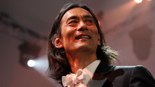 Un homme aux cheveux longs regarde vers sa gauche en souriant.