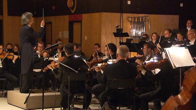 Kent Nagano dirige un orchestre dans la salle Teueikan de Maliotenam