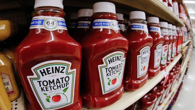 Des bouteilles de ketchup Heinz alignées sur une étagère de supermarché.