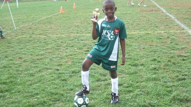 Une photo de Kevin prise quand il était un petit garçon. Il tient ue trophée et pose le pied sur un ballon de soccer, au milieu du terrain.