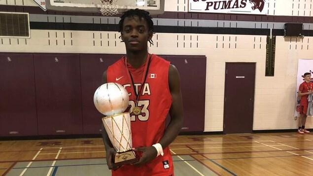 Kevin sur un terrain de basketball porte un énorme trophée surmonté d'un ballon.