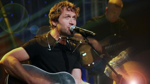 Le chanteur Kevin Parent devant un micro, guitare à la main.
