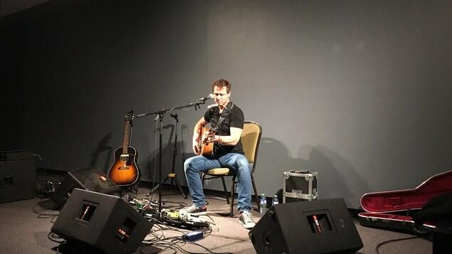 Kevin Parent est assis et joue de la guitare.