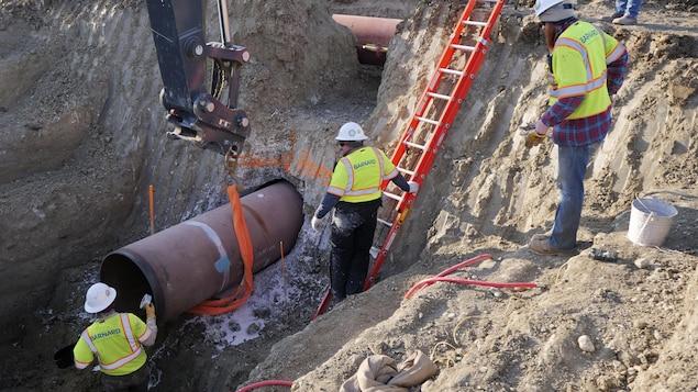 Des travailleurs sont proches d'une canalisation située sous terre, dans une tranchée.