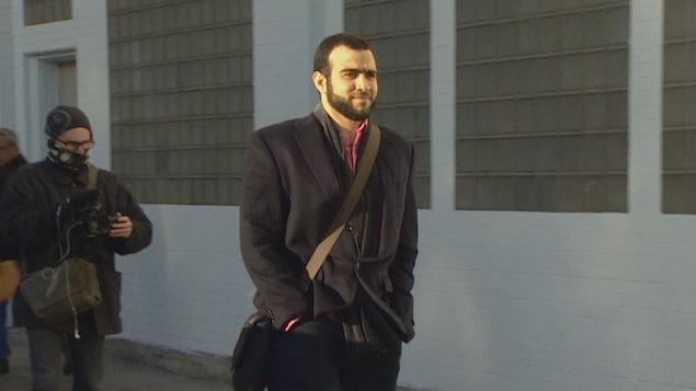 omar Khadr marche dans la rue, les mains dans les poches.