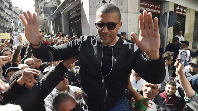Khaled Drareni, porté par des manifestants dans une rue bondée, salue la foule.