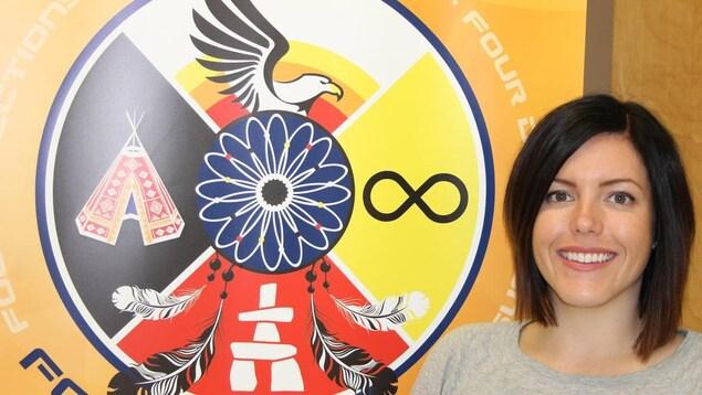 Une femme souriant à la caméra à côté d'un logo avec des symboles des Premières Nations, des Métis et des Inuits.