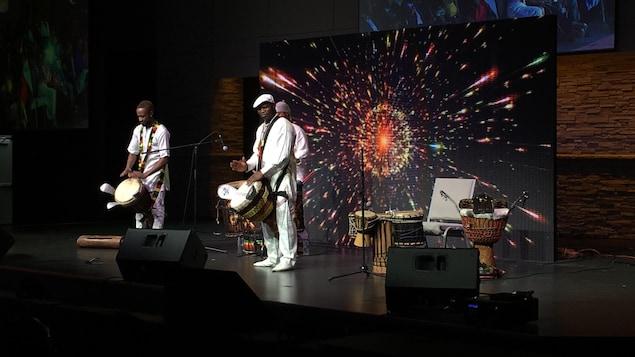 Trois hommes sur scène jouent de la musique africaine.