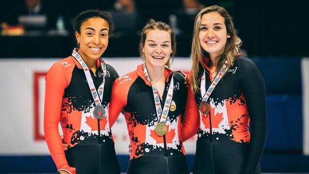Kim Boutin sur la plus haute marche du podium avec une médaille d'or au cou. À côté d'elle, deux autres athlètes avec des médailles d'argent et de bronze.