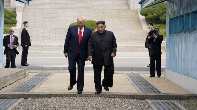 Donald Trump et Kim Jong-un se promènent dans la zone démilitarisée, sous l'oeil de militaires et de journalistes.