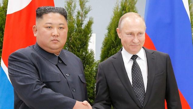 Côte à côte, les deux hommes se serrent la main en regardant droit devant eux. Seul Vladimir Poutine esquisse un sourire.