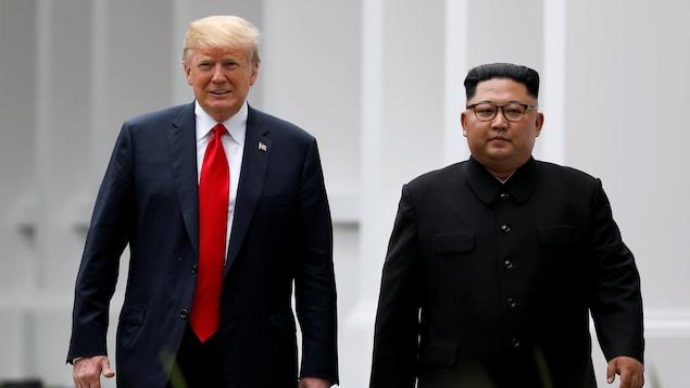 Donald Trump et Kim Jong-un marchent côte à côte.