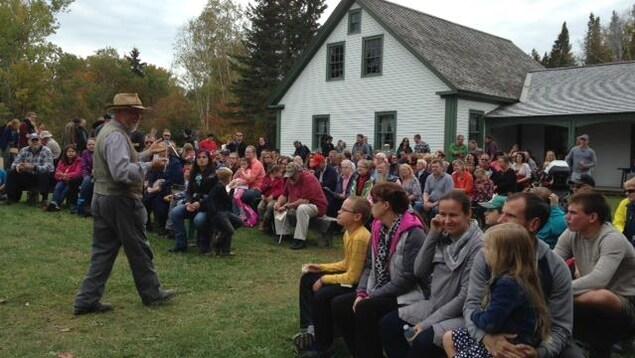 Un interprète en costume du 19e siècle parle à une foule de touristes devant une maison patrimoniale.