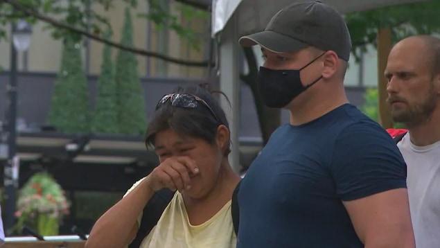 Un homme avec un masque sanitaire et une femme en pleurs.