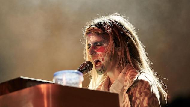 La femme dont le visage est maquilé, est assise et chante dans un micro.