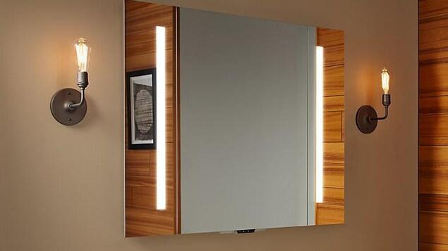 Une photo montrant un miroir installé dans une salle de bain. On peut apercevoir un petit appareil électronique dépassant du bas du miroir.