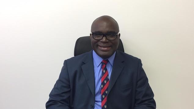 Kouamé N'Goandi assis sur une chaise de bureau.