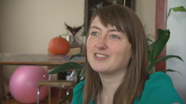 Une jeune femme sourit durant une entrevue.
