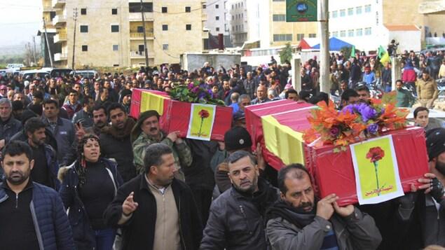 Des Kurdes transportent deux cercueils dans les rues d'une ville.