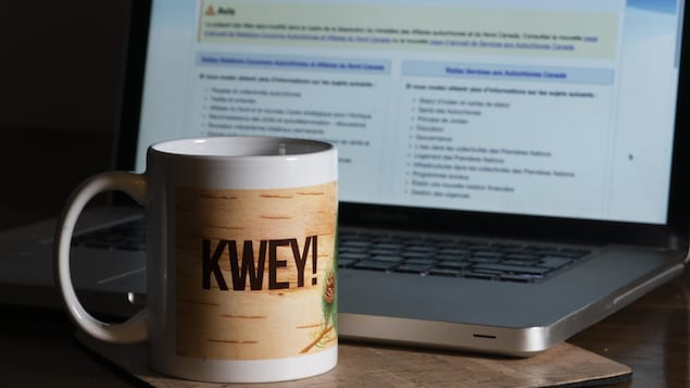 Une tasse sur laquelle il est écrit kwey, devant un écran d'ordinateur portable.