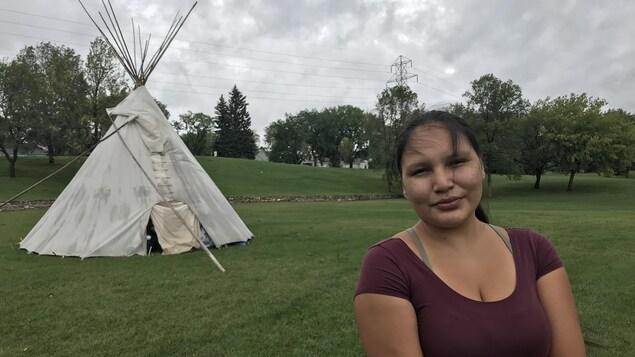 Une femme est devant un tipi dans le parc Victoria de Saskatoon.