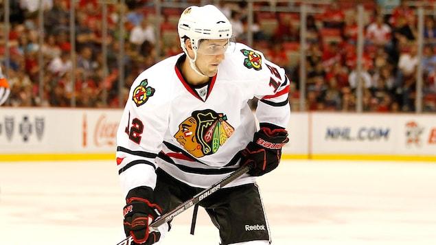 Un joueur de hockey droitier, vêtu de l'uniforme blanc et noir des Blackhawks de Chicago, s'apprête à patiner pendant un match préparatoire de la LNH.