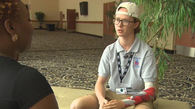 Un jeune homme, casquette à l'envers, prothèse au bras gauche, assis, discute avec une animatrice de Radio-Canada.