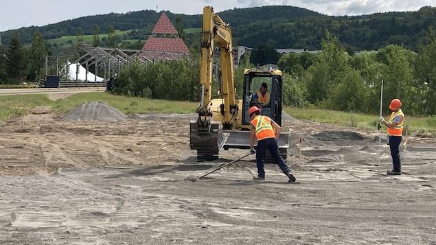 Une pelle mécanique au travail avec des ouvriers.