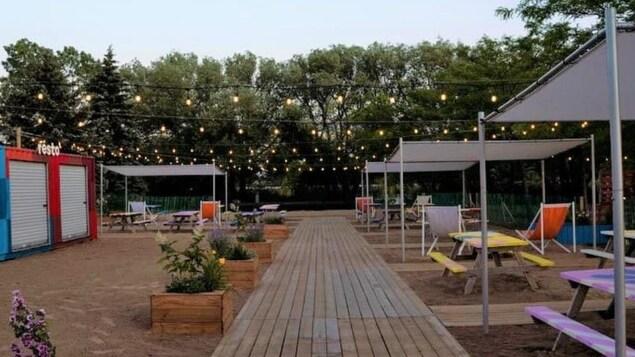 Chapiteaux avec tables de pique-nique, plantes et lumières décoratives.