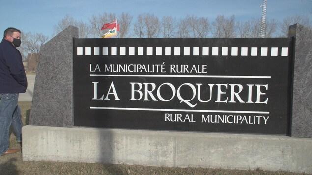 Un homme masqué marchant à côté du panneau de la municipalité rurale de La Broquerie.