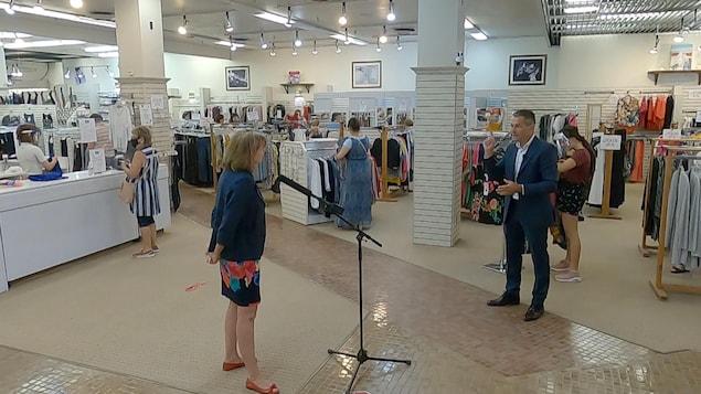 La copropriétaire du magasin Laliberté, Lucie Morisset, en entrevue avec Bruno Savard, à l'intérieur du magasin avec des clients autour.