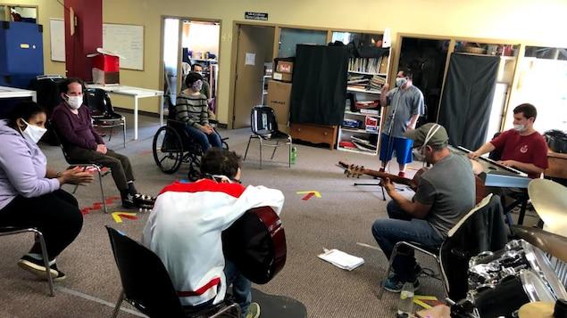 Des personnes assises en rond. Deux d'entre elles jouent de la guitare.