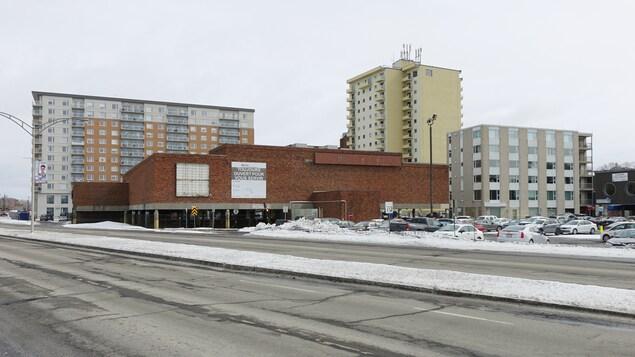 L'édifice de la Grande Place près d'un stationnement et d'autres immeubles du centre-ville de Rimouski.