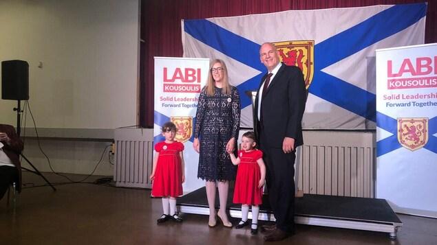 Labi Kousoulis et sa famille devant un drapeau de la Nouvelle-Écosse.